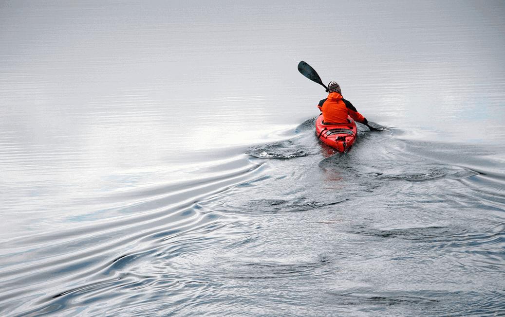 kayaker in red kayak paddling away