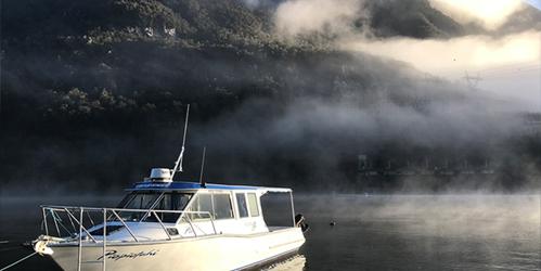 Cruise boat among mist at West Arm, Lake Manapouri