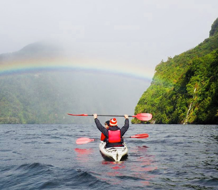 Two kayakers in double kayak with rainbow above them